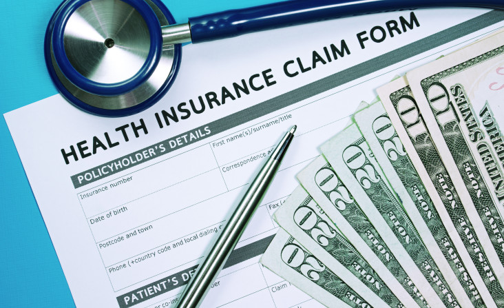 Health insurance claim form with money and stethoscope for insurance concept